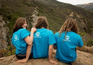 three young girls sitting on top of a mountain