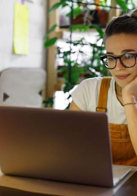 girl wearing glasses working on her laptop