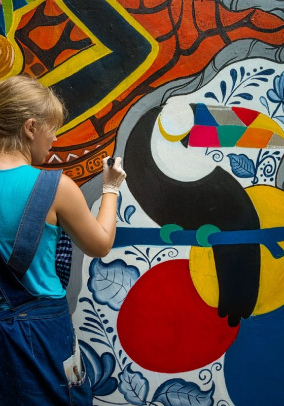 Cheerful young woman painting on the wall.